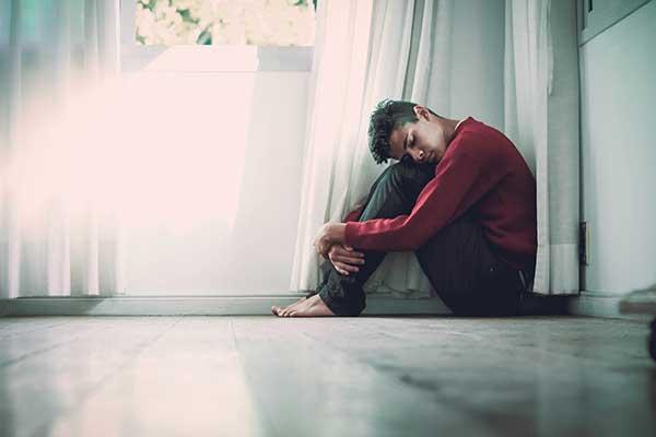 Man sitting on floor not feeling mentally well
