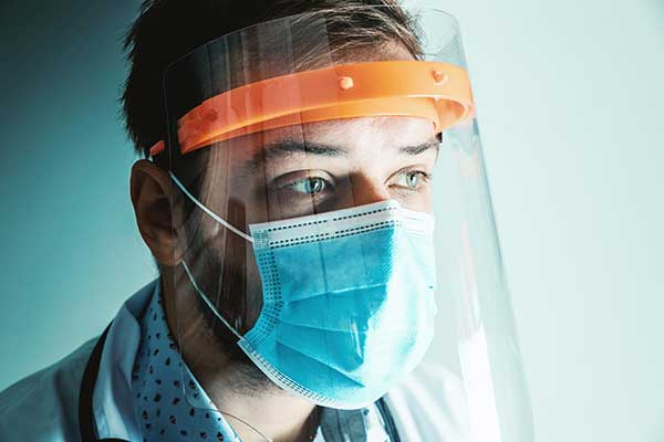 Healthcare worker in mask and faceshield